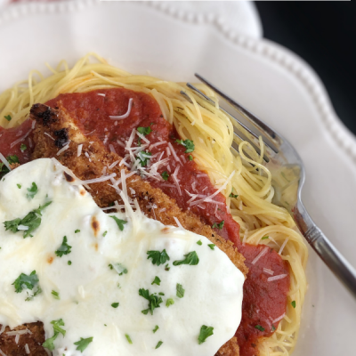 This easy Chicken Parmesan over Angel Hair Pasta recipe is good enough for company. Panko breading adds crunch and fresh mozzarella bubbles on top. Divine!