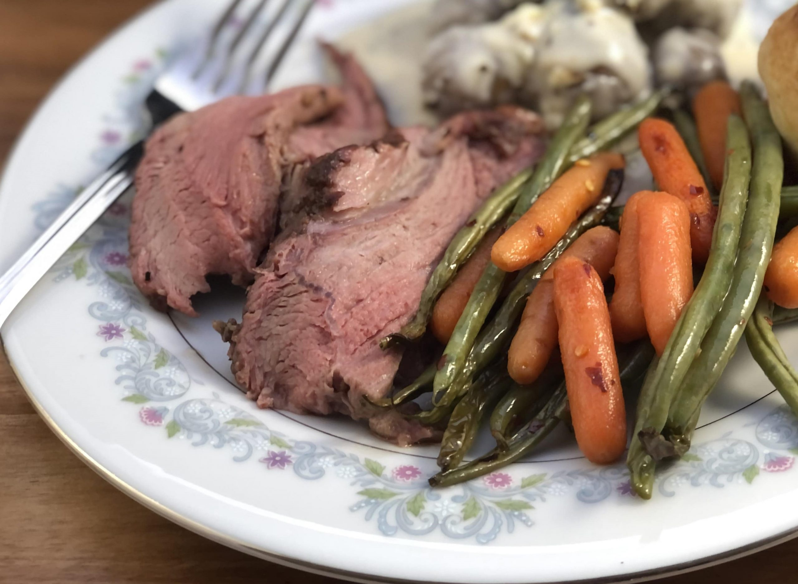 Sliced leg of lamb on a plate with green beans and carrots.