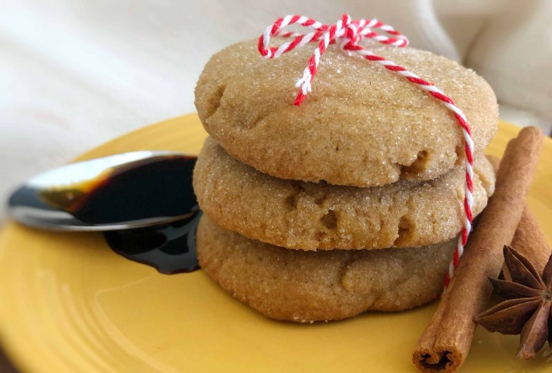 Thick molasses cookies stacked 3 high and tied with red and white baker's string. Garnished with a spoon of molasses drizzling on the plate, cinnamon stick, and star anise.