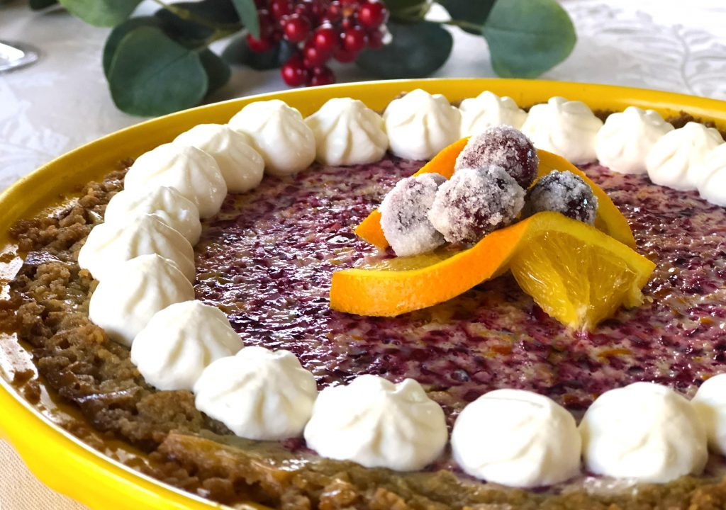 Whole cranberry orange pie in yellow Fiesta pie pan garnished with whipped cream, orange slices, and frosted cranberries.