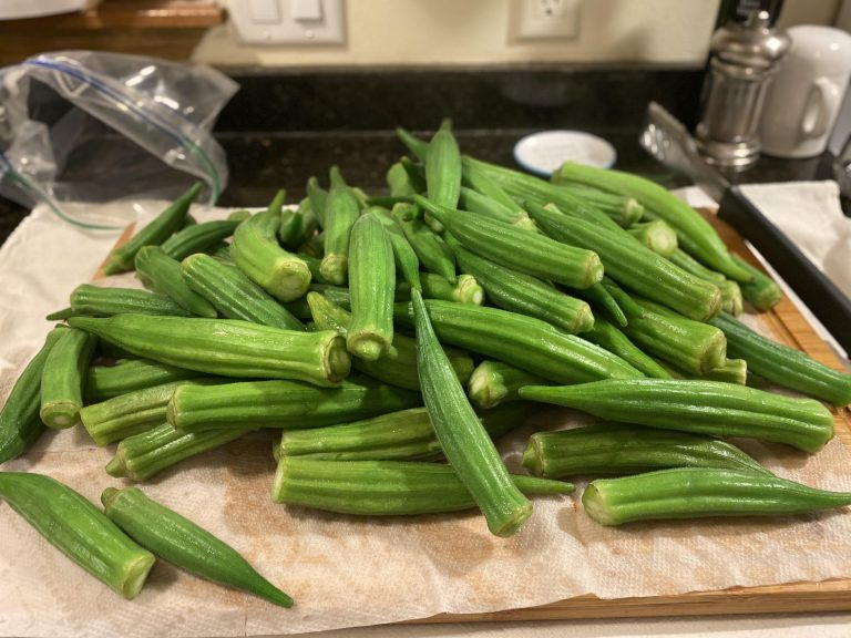 Whole okra pods on paper towel.